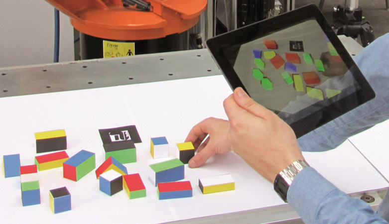 การโปรแกรมหุ่นยนต์ด้วยการกำหนดงาน โดยการสาธิตภาระงาน จากลักษณะการเคลื่อนไหว พร้อมกับนำมาแสดงด้วยความจริงเสริมที่เครื่อง Tablet-PC